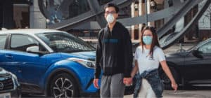 boy and girl walk with masks on near cars